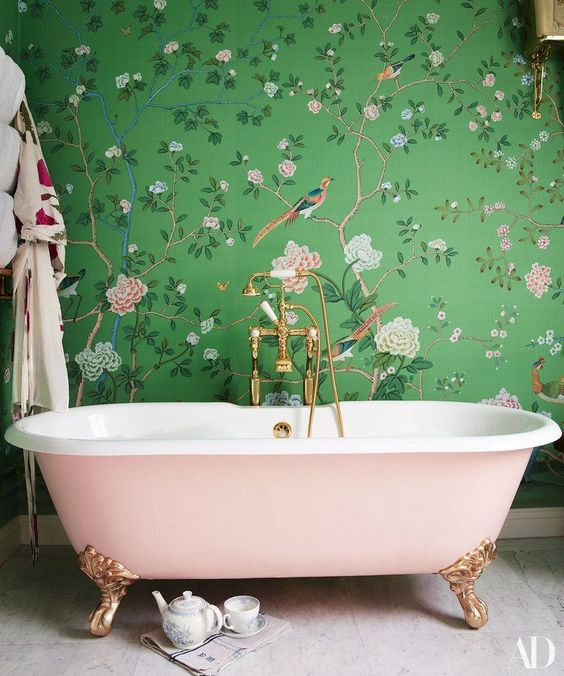a girlish space with green and pink floral print wallpaper and a blush  bathtub for a
