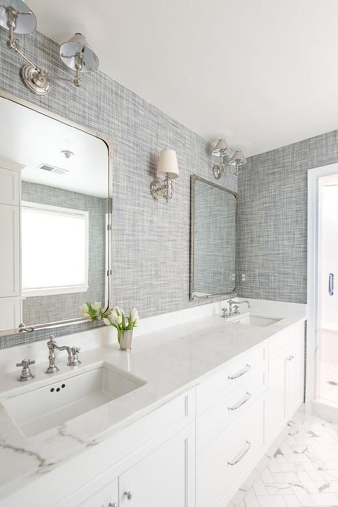 Beautiful white and gray bathroom is clad in gray textured wallpaper  accenting marble herringbone tile floors framing a white dual vanity fitted  with