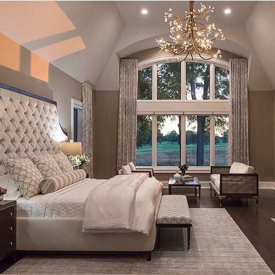 Check out that fabric headboard. Love the high ceilings and the arched  window