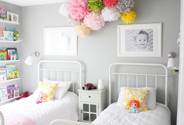 A pair of little ladies sleep side by side in this lovely set up, complete  with a colorful floral decoration that lives right in the middle.
