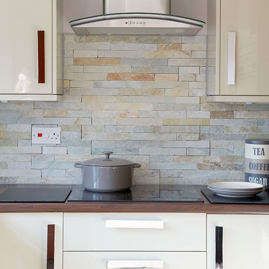 Natural coloured slate wall tiles are used complement this cream modern  kitchen http://