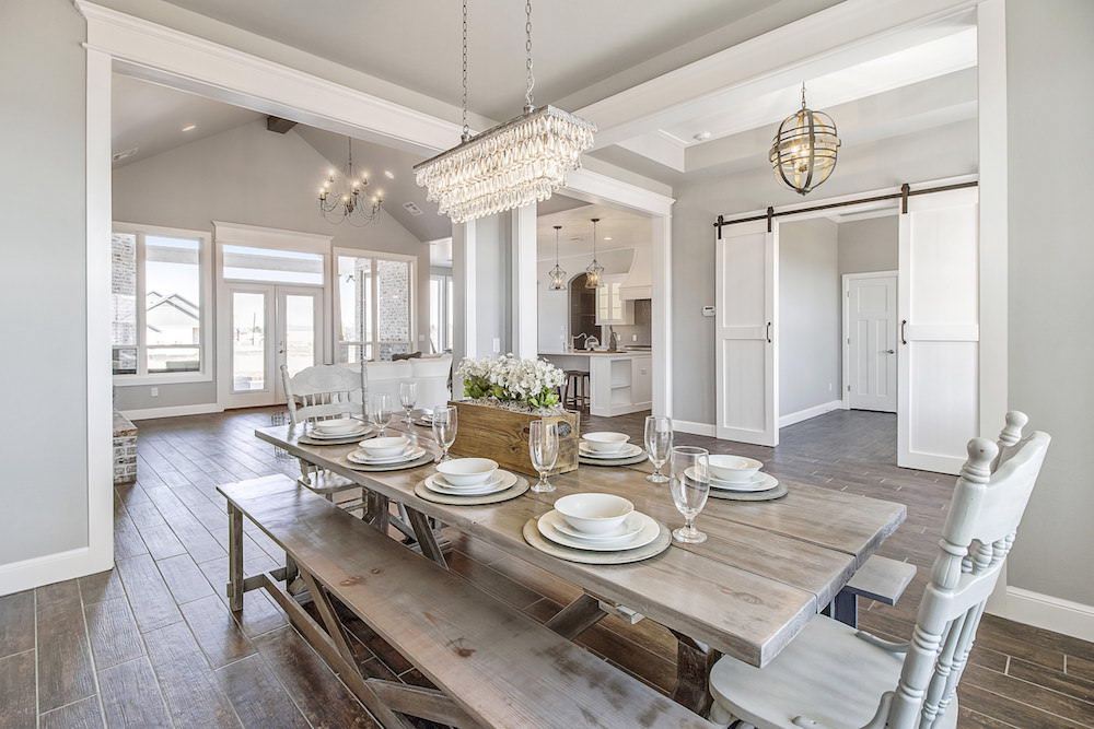 Light rustic dining room table with bench seating in large dining rooms  space. Long chandelier