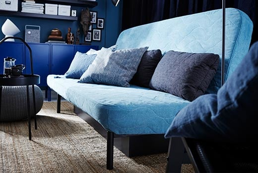 A light blue NYHAMN sofa bed with blue accent cushions