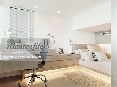 Desk and bed in modern bedroom - Stock Photo