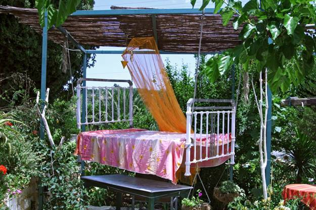 Hanging outdoor bed with wooden sunshade and light curtain